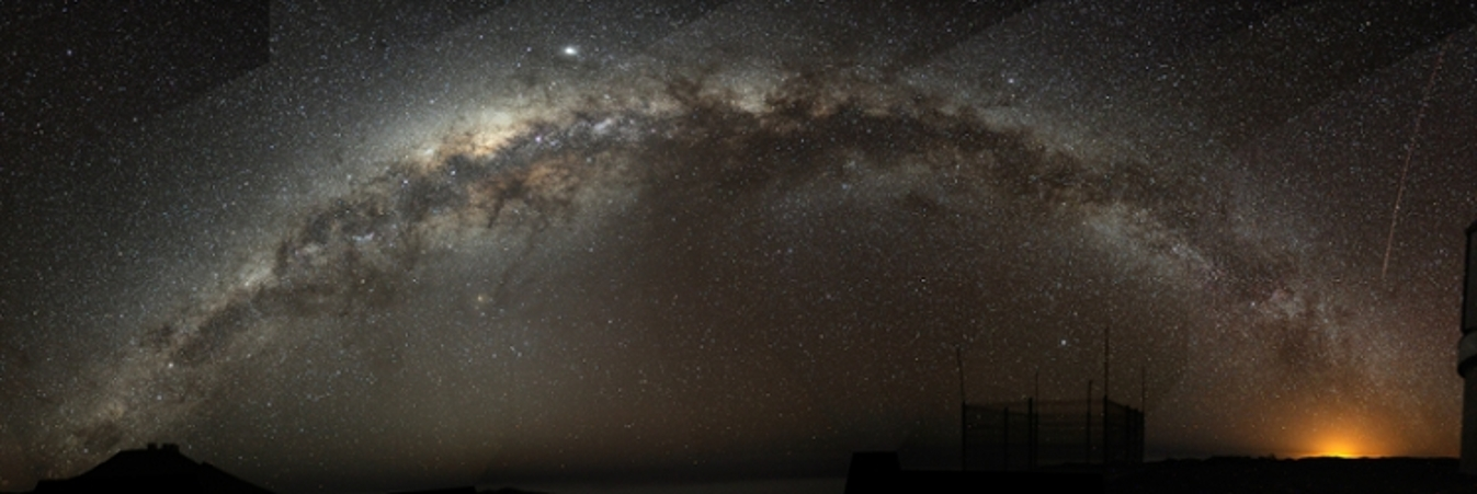 <strong>Overarching via lactea. </strong> The Milky Way arch emerging from the Cerro Paranal, Chile, on the left, and sinking into the Antofagasta's night lights. The Magellanic Clouds are visible on the left side, and a plane has left a visible trace on the right, along the Vista enclosure. Courtesy Bruno Gilli; ESO. Creative Commons Attribution 4.0.