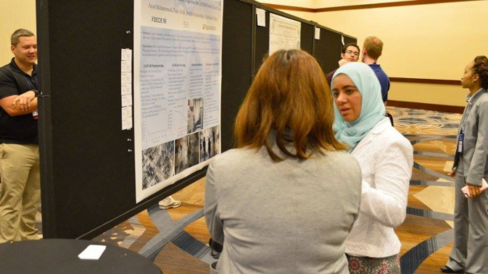 <strong> Meeting of the minds. </strong> Ayat Mohammed explains her poster to an XSEDE16 attendee. Courtesy XSEDE.