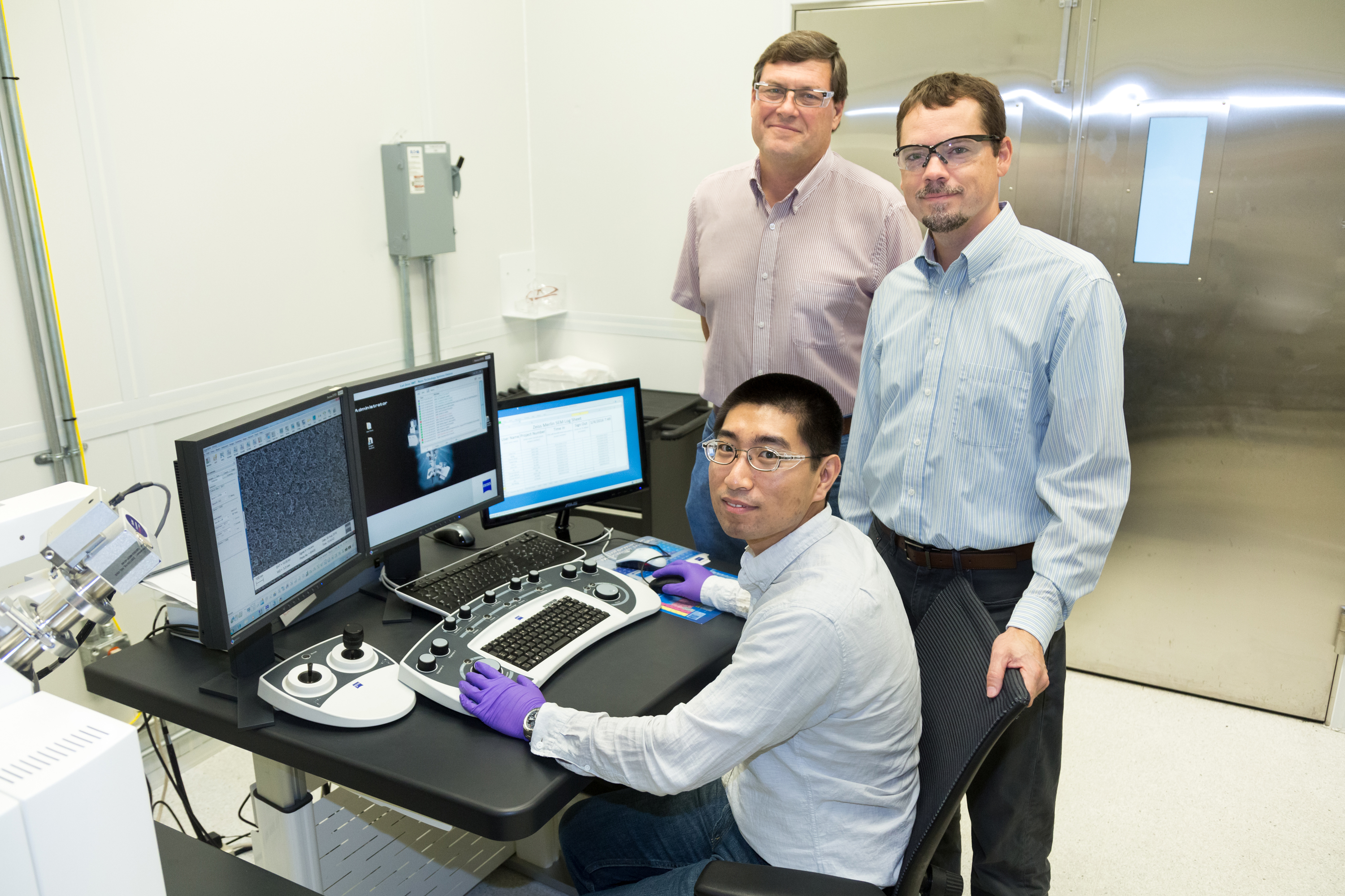 <strong>Little bit of luck. </strong> ORNL's Yang Song (seated), Dale Hensley (standing left) and Adam Rondinone examine a carbon nanospike sample with a scanning electron microscope. Photo courtesy ORNL.