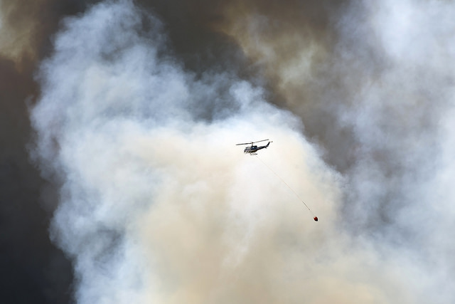 <strong>A drop in the bucket. </strong> A helicopter carries fire retardant to a wildfire burning in a Fort McMurray neighborhood. Deep learning is informing responders so they can react to natural disasters more efficiently — and save lives. Courtesy Premier of Alberta; Chris Schwarz; Government of Alberta. <a href= 'https://creativecommons.org/licenses/by-nd/2.0/legalcode '>(CC BY-ND 2.0) </a>