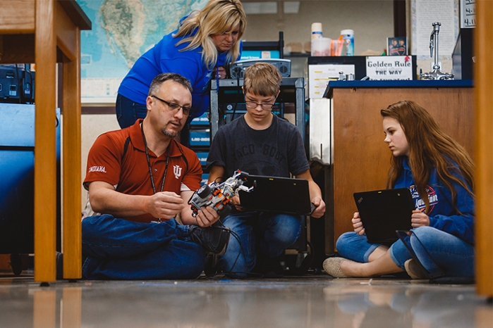 <strong>Learning from the Mindstorm master.</strong> Science teacher Amy Glassco watches as IU staffer Tony Brazzell (left) explains one of the finer points of robotics. Brazzell is a mentor/coach for local youth robotics clubs. Courtesy Indiana University.