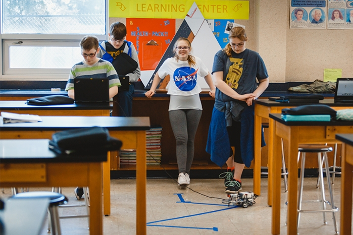 "<strong>Future scientists?</strong> Steven Case (far left) and Hannah Burcham (center, in NASA shirt) are two of the robots' biggest fans. ""I love science,"" said Burcham. Courtesy Indiana University."