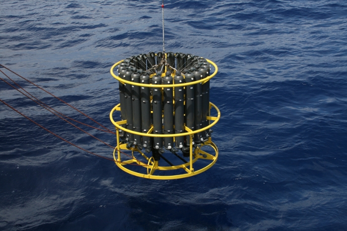 <strong>A CTD device</strong> that measures water conductivity (salinity), temperature and depth is mounted underneath a set of water bottles used for collecting samples at varying depths in a column of water. Courtesy Tara Clemente, University of Hawaii.
