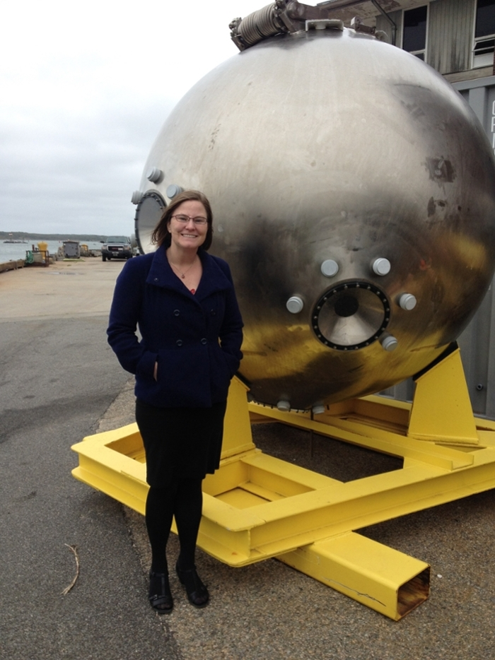 <strong>Sample collection.</strong> Bonnie Hurwitz next to the metal pod that serves as the main chamber for the Alvin submersible that scientists operate to collect samples from the deepest parts of the ocean not accessible to people. Courtesy Stefan Sievert, Woods Hole Oceanographic Institution.