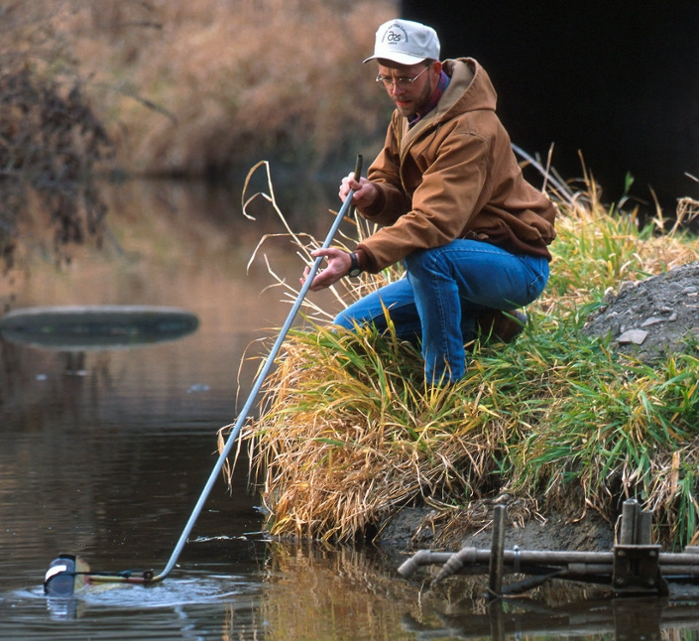 <strong>Raw data.</strong> An agricultural research technician collects weekly water samples from a creek to determine the effects of farming practices on water quality. A new platform, GeoEDF, may help officials combine this information with other data to make better decisions. Courtesy USDA.