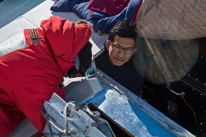 <strong>Getting their hands cold.</strong> Dan Marrone and Junhan Kim install a mirror on the roof of the South Pole Telescope in Antarctica. Courtesy Junhan Kim, University of Arizona.