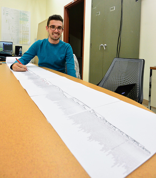 <strong>Long history.</strong> Bioinformatics undergraduate student Thomas Kidder working with a printout of the 1KP green plant phylogeny. The paper outlining the gene families of the plant tree of life measures about 50 feet. Courtesy Mike Barker.