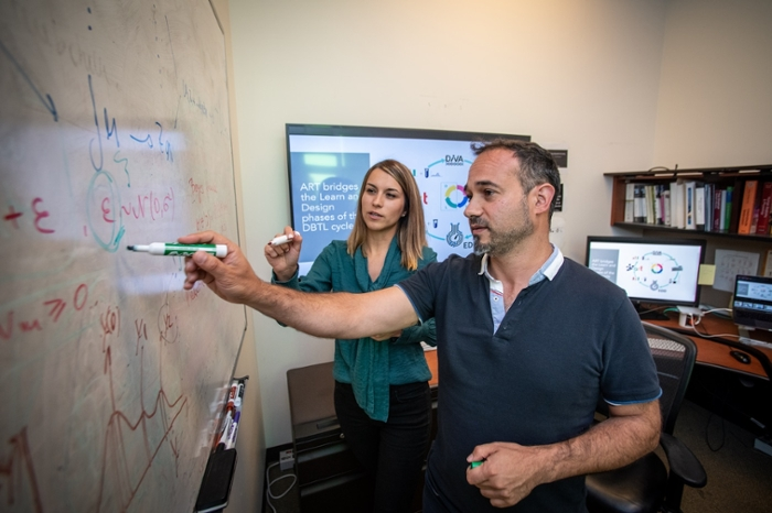 <strong>Metabolic engineering.</strong> Tijana Radivojevic (l) and Hector Garcia Martin tackle mechanical and statistical modeling, data visualizations, and metabolic maps at the Agile BioFoundry. Courtesy Thor Swift, Berkeley Lab.